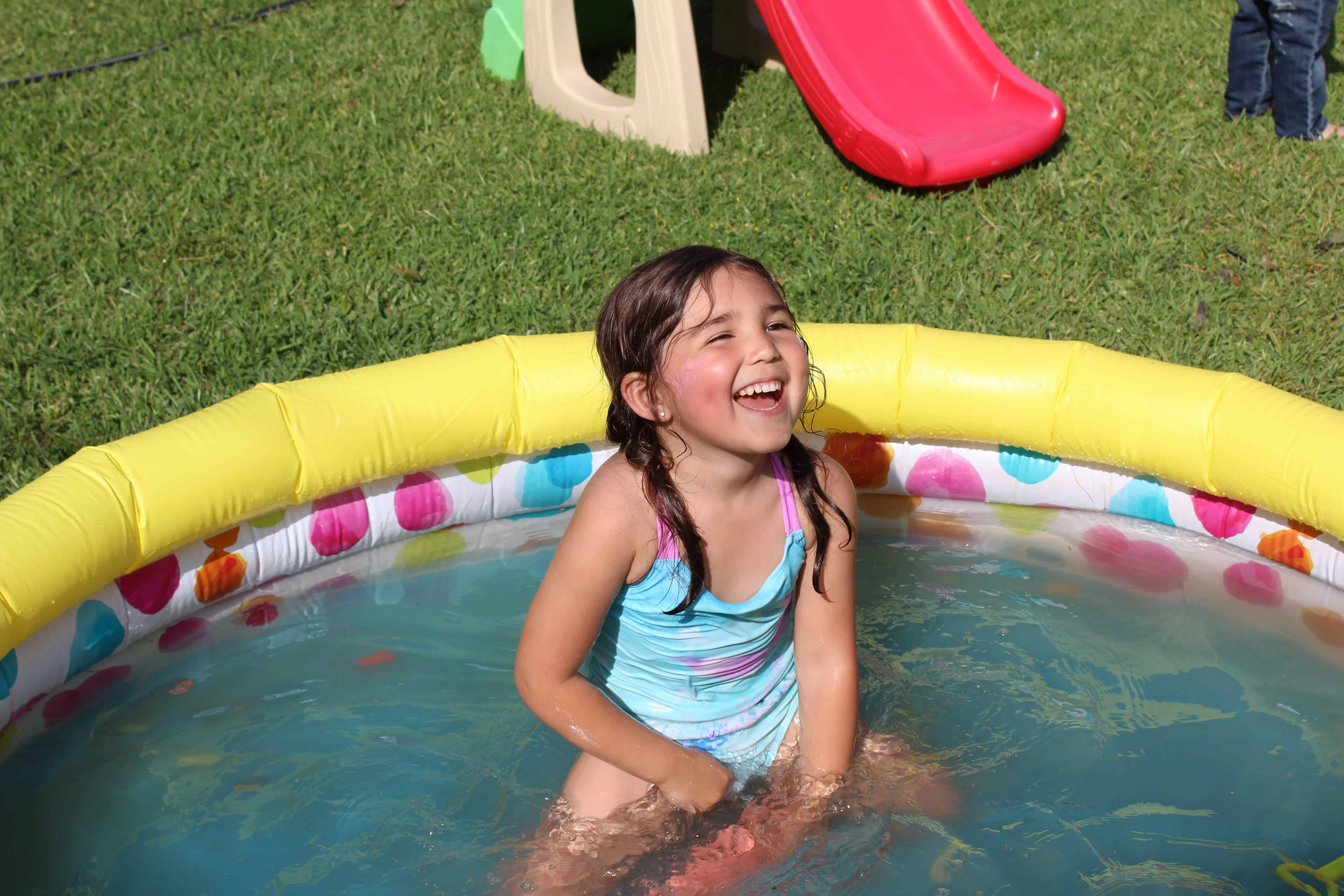 Little girl smiling in inflatable pool