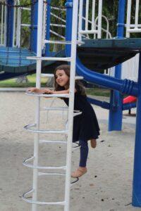 a little girl climbing a ladder at the park