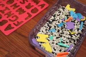 sensory bin filled with beans and foam ABC puzzle pieces