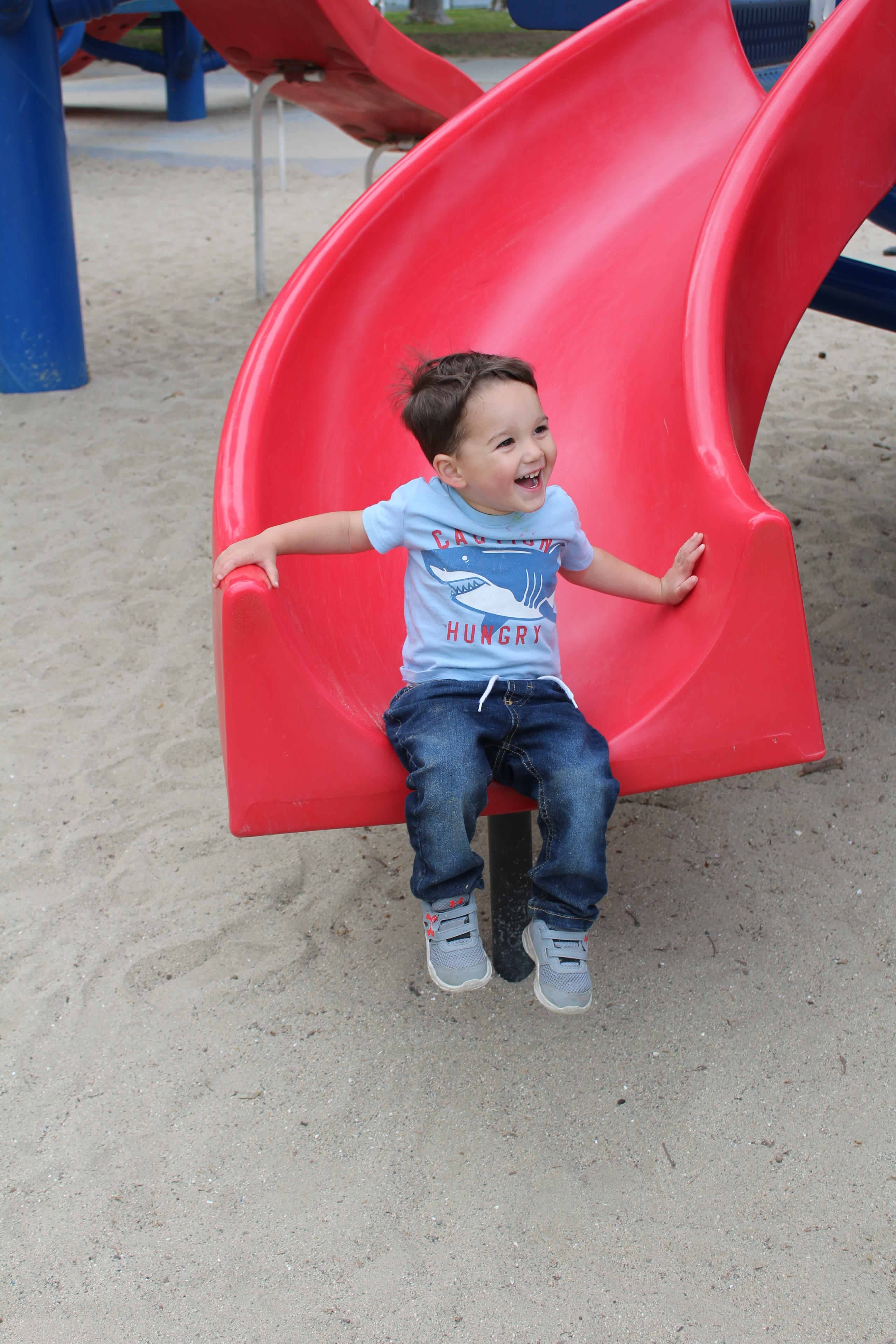 A preschool boy sliding down a red slide with a big smile on his face