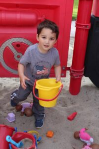 a little boy playing in the sand with a yellow bucket