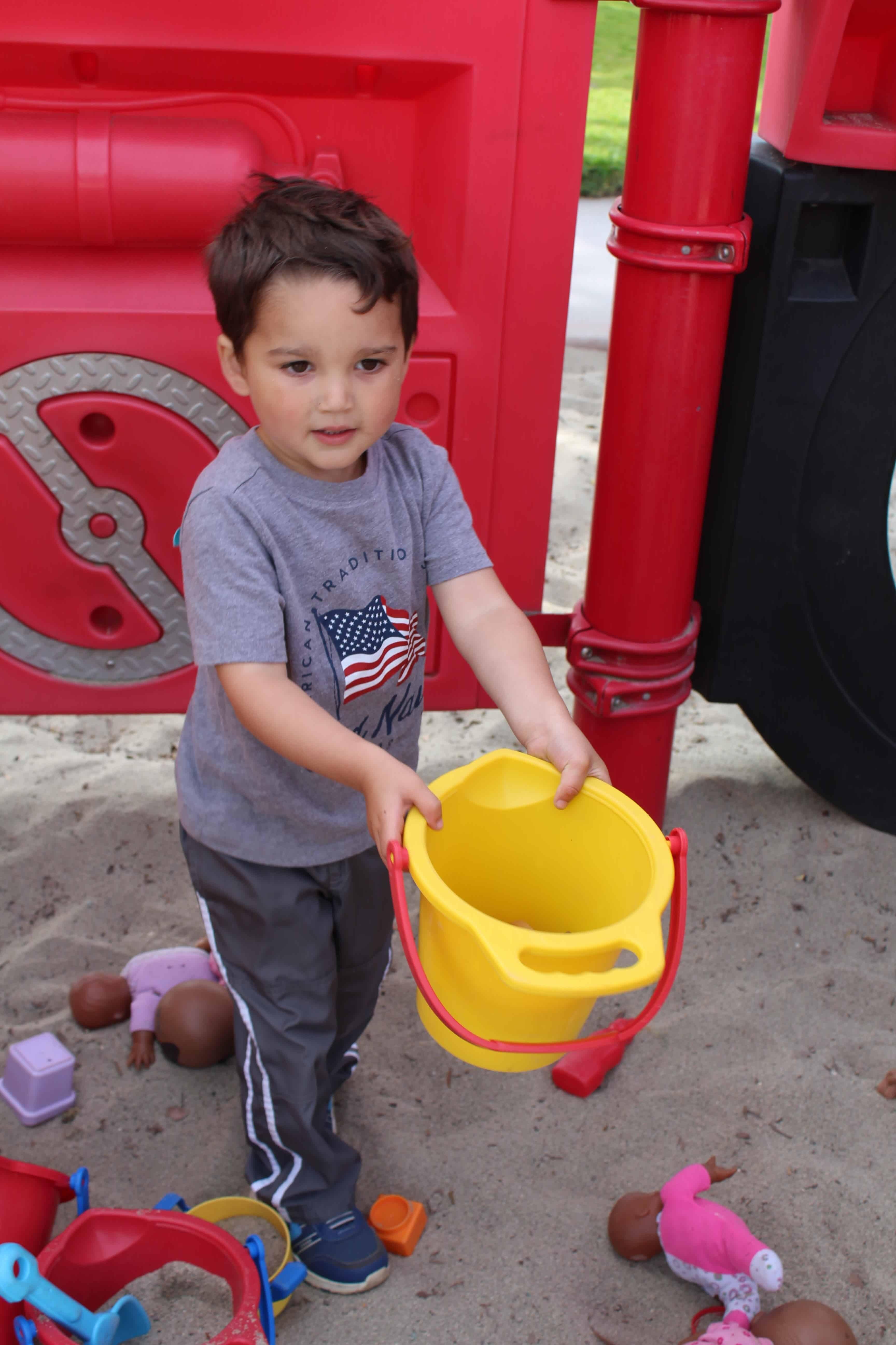 Toddler holding empty bucket.