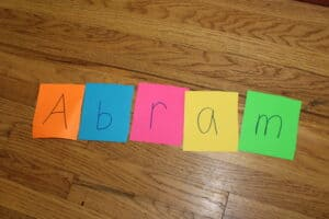 "colorful index cards spelling out the word ""abram,"" with one letter on each card"