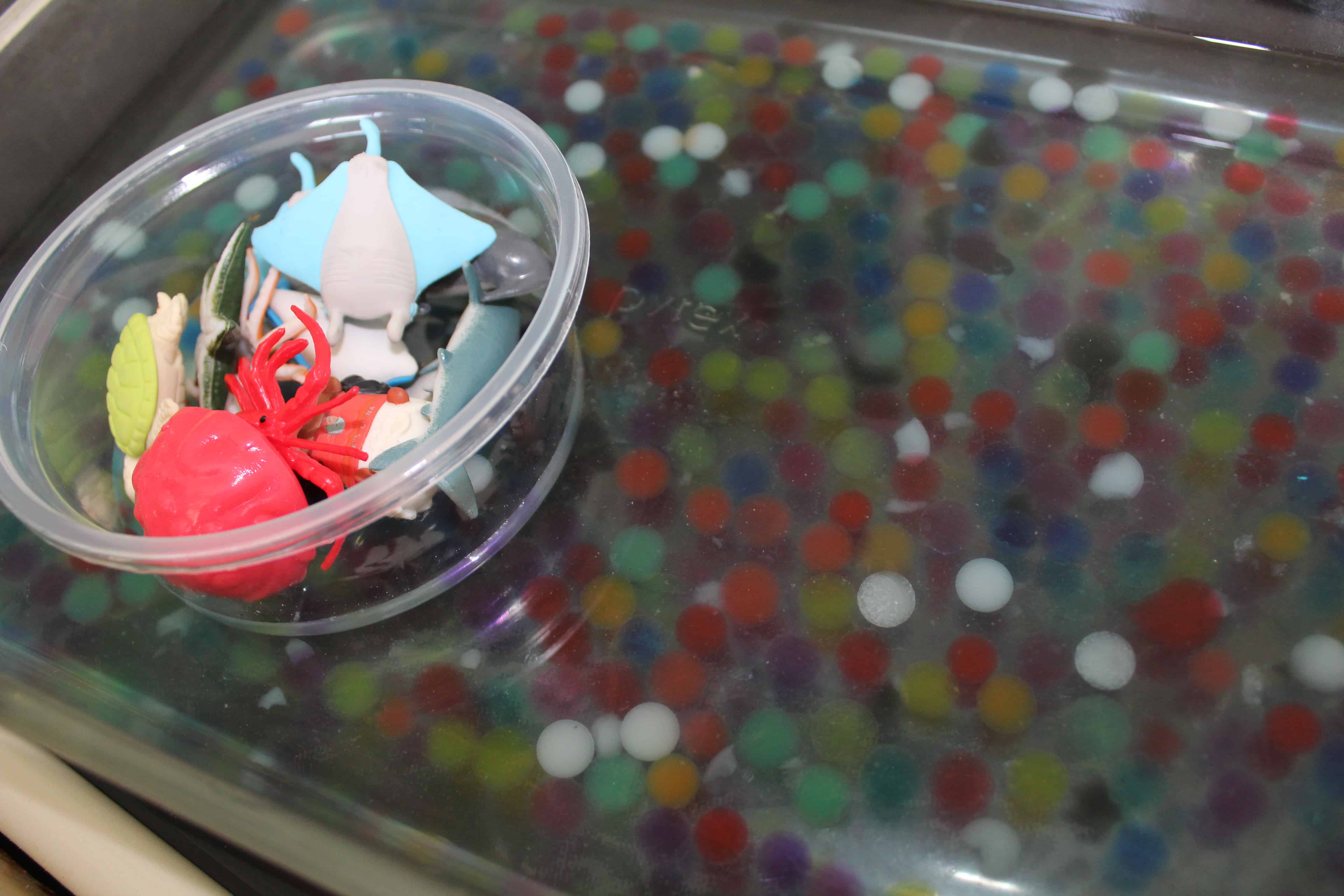 a shallow dish filled with water beads and plastic sea creatures