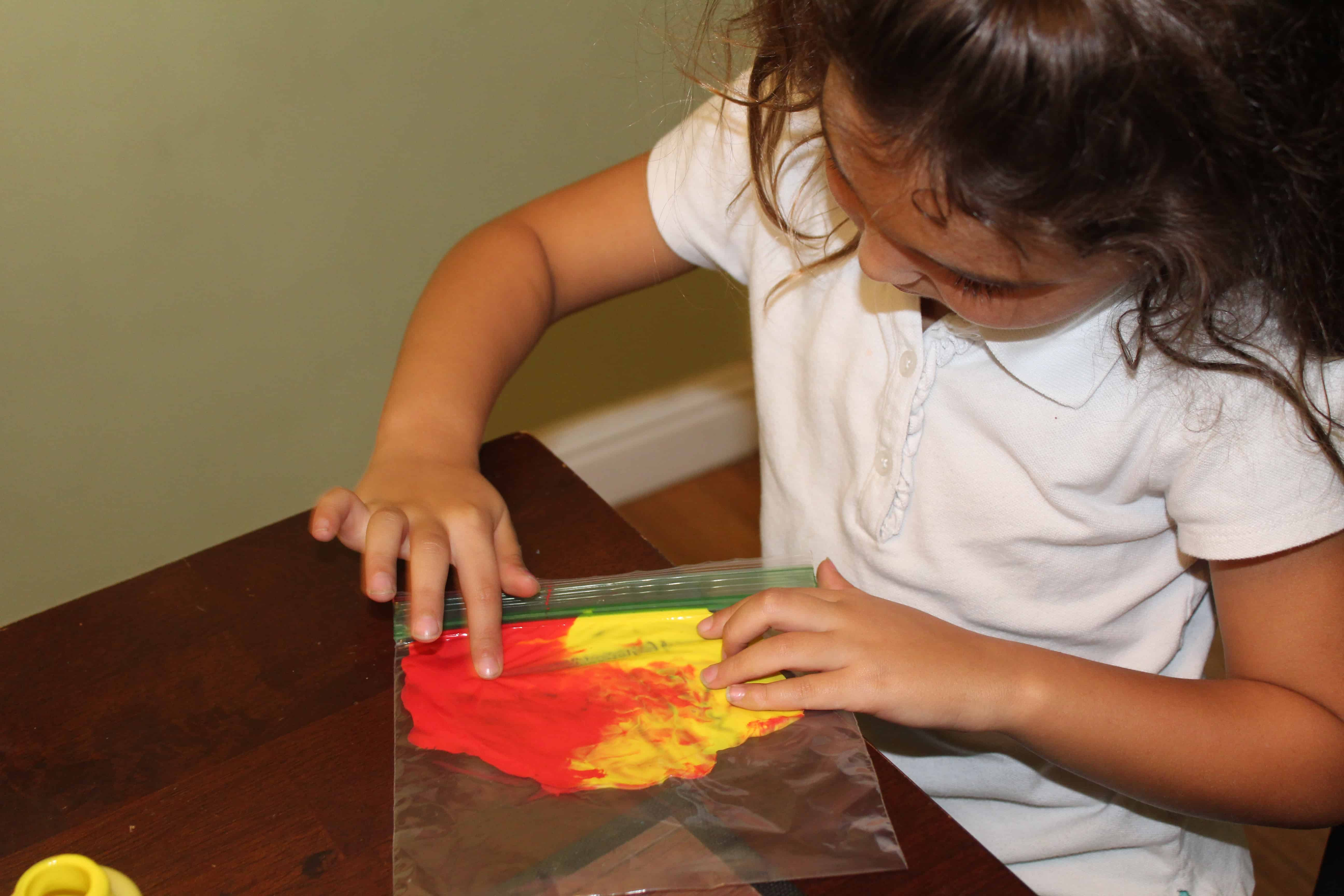 little girl mixing paint colors in a ziploc bag