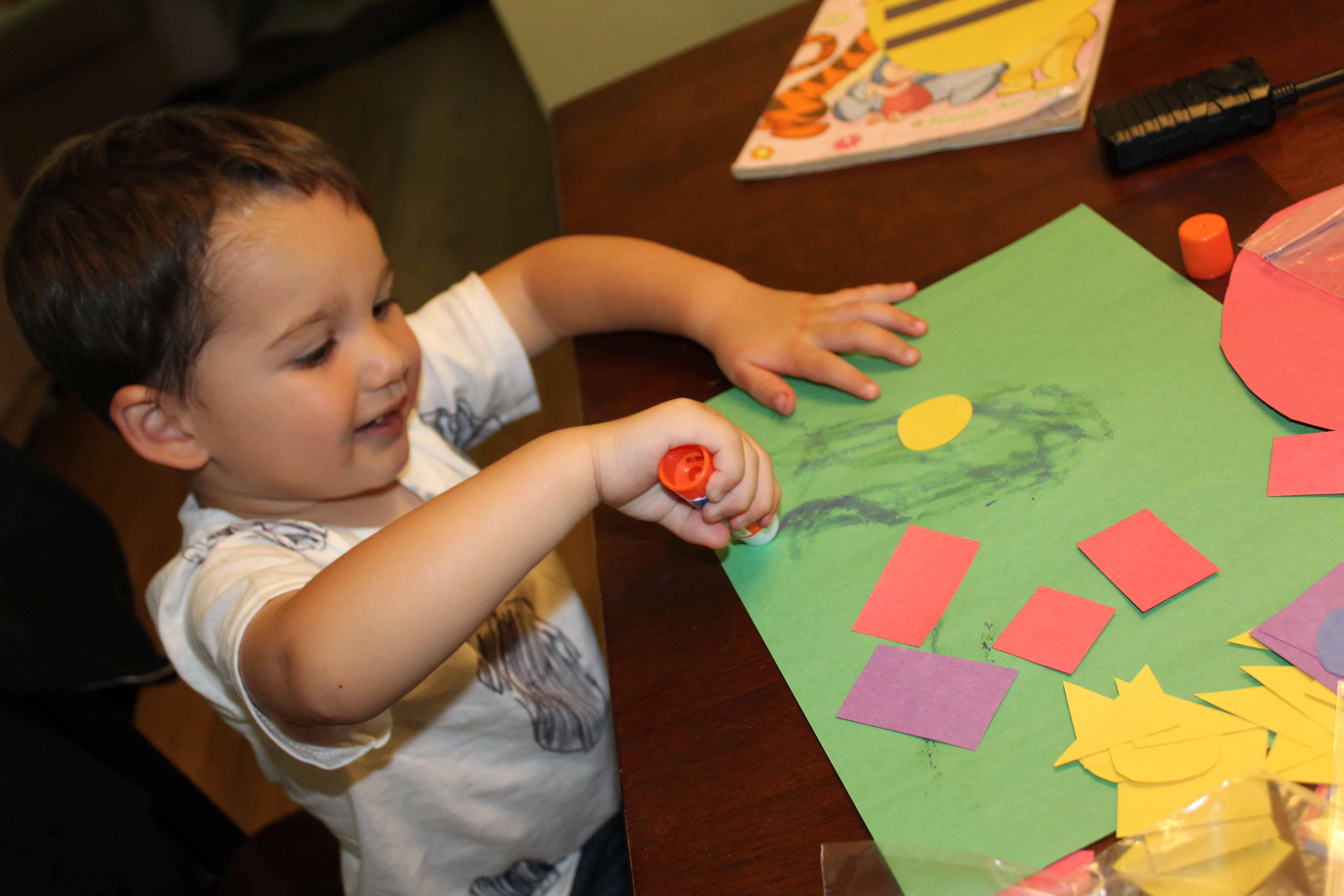 preschooler gluing construction paper shapes onto paper