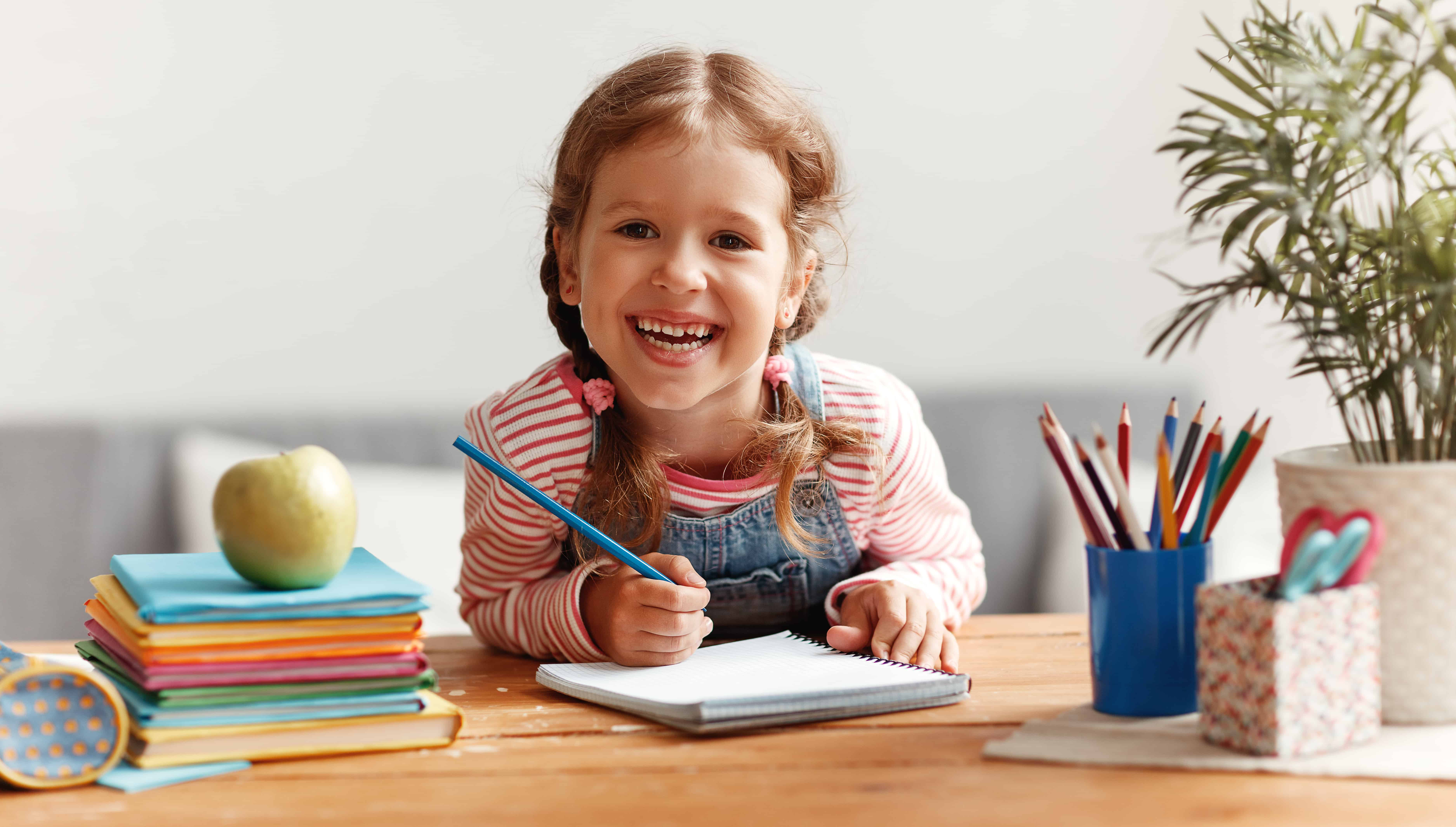 little girl smiling and writing in a notebook