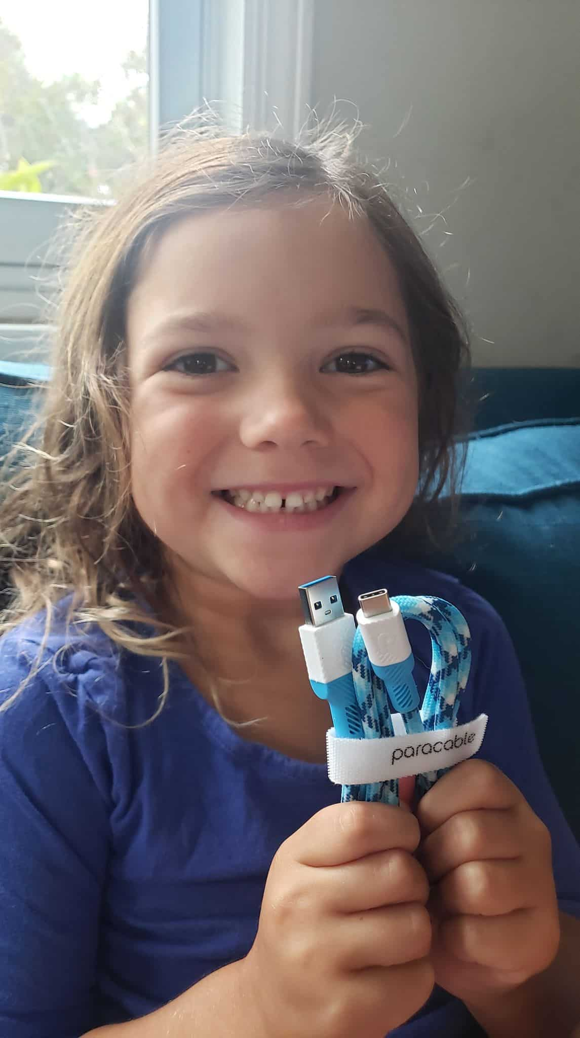 Smiling little girl with baby blue paracord cable.