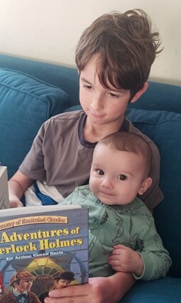 big brother reading to his baby brother