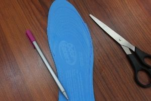 Odor eater customizable insoles trimmed next to scissors and a pen