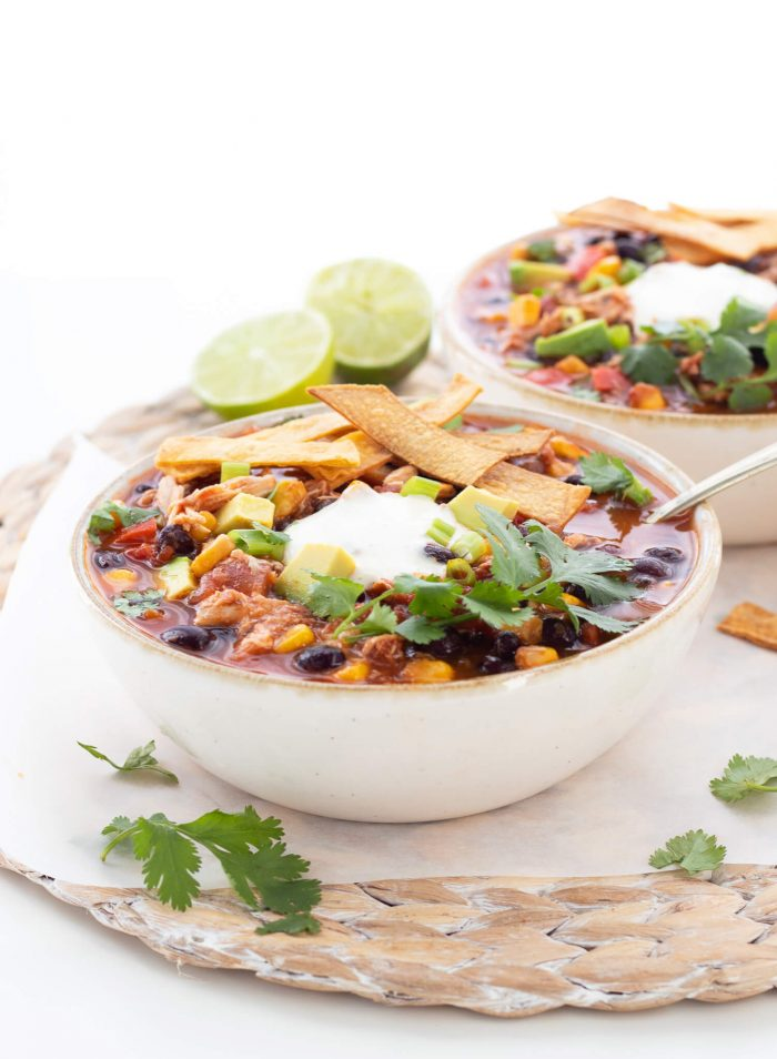 chicken tortilla soup topped with sour cream and tortilla strips