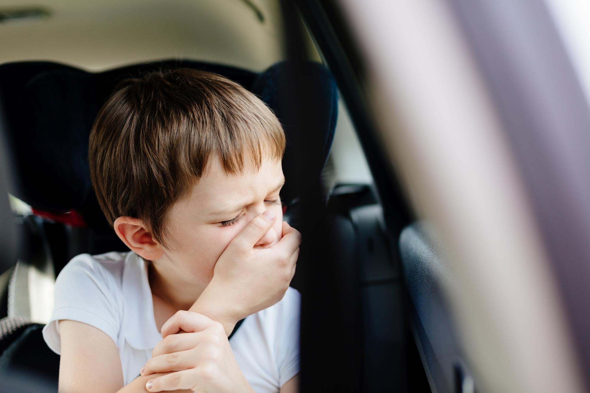 child with motion sickness in the car