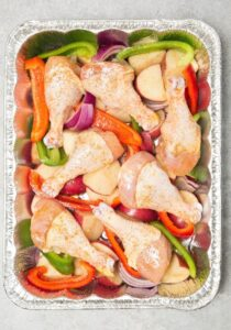 chicken and veggies freezer meal prepped in a tin pan