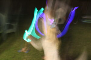 kid dancing with glow sticks; blurry