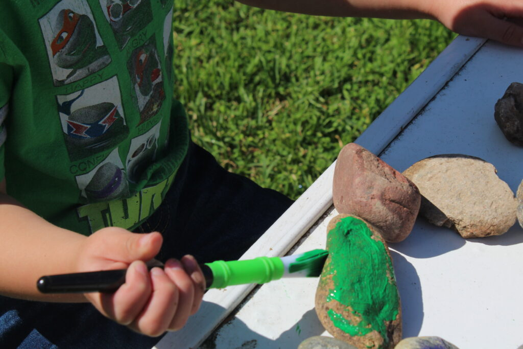 toddler painting a rock green
