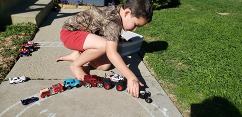 little boy playing with cars outside