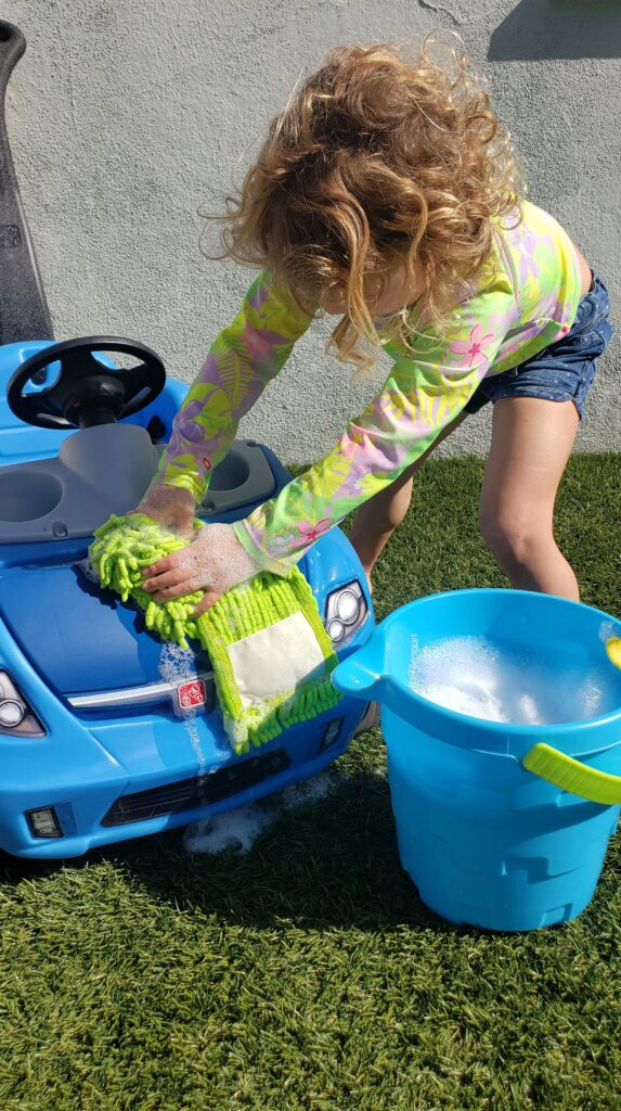 Little girl washing ride on toy car