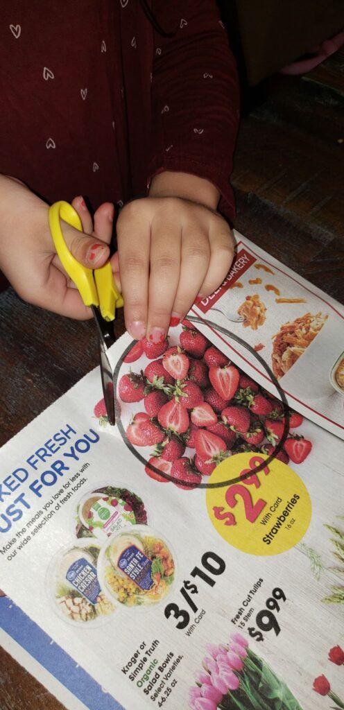 preschooler cutting practice using grocery ad