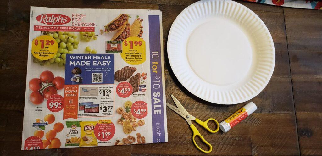 grocery ad; papper plate; scissors; glue