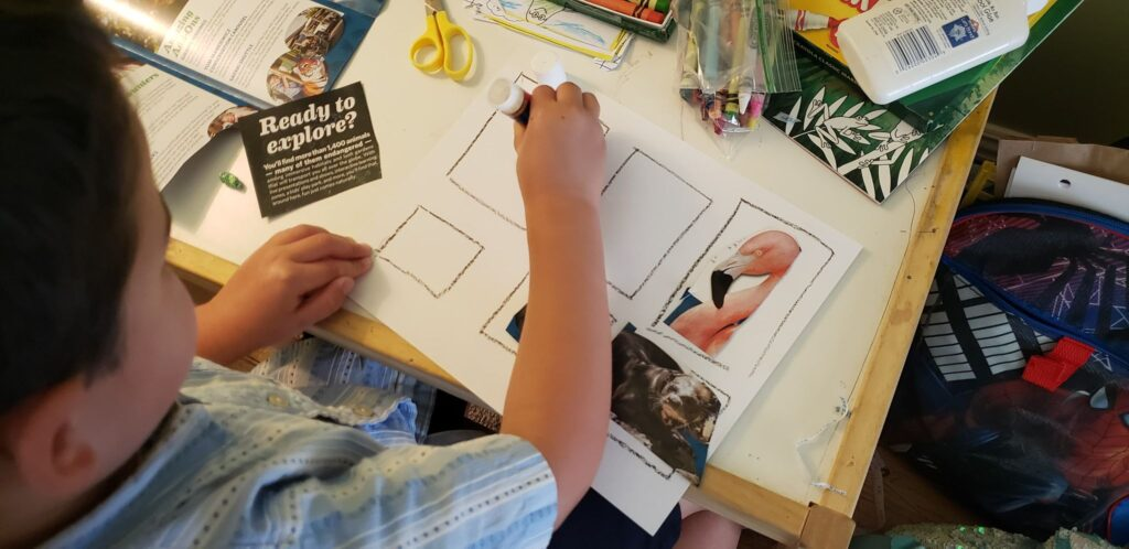 toddler gluing animals onto paper zoo