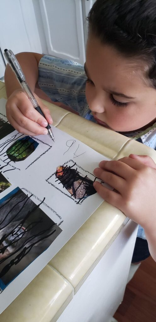 preschooler writing name on Make a Zoo page