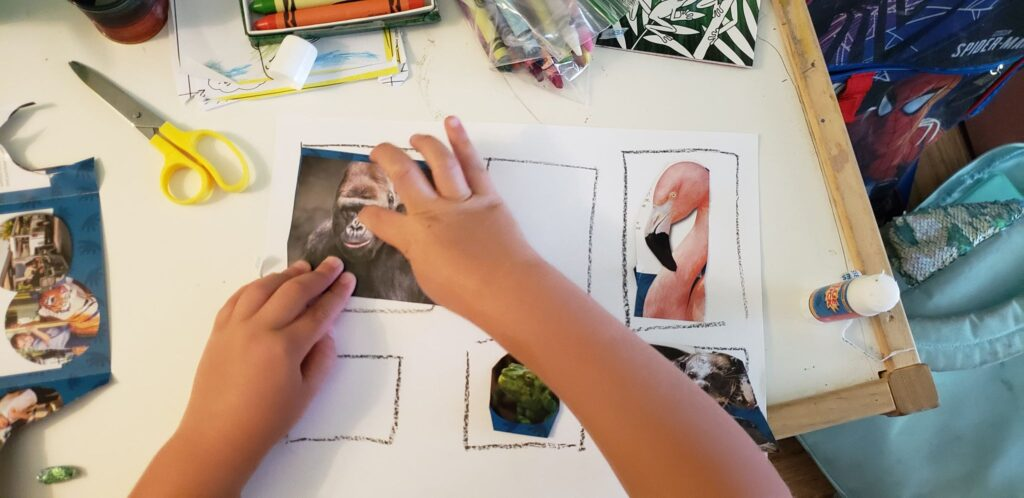 toddler gluing cut out animals onto paper