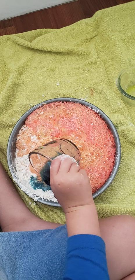 kid pouring vinegar into baking soda