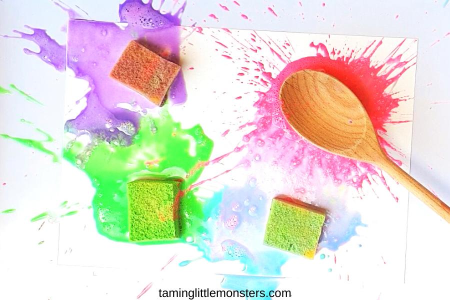 a spoon hitting a paint filled sponge