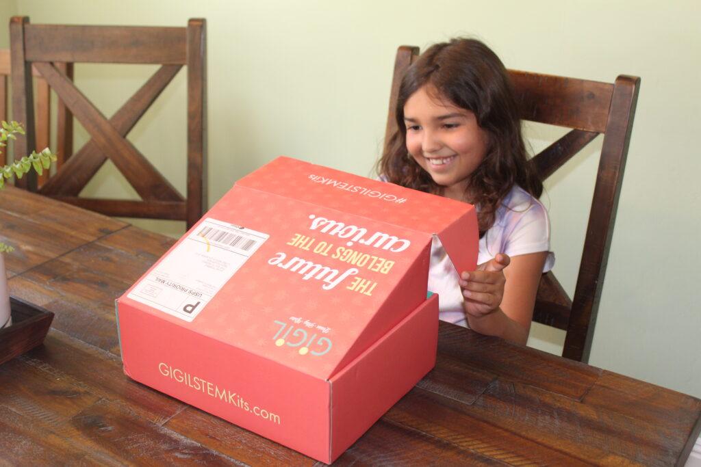 child opening gigil stem kit box